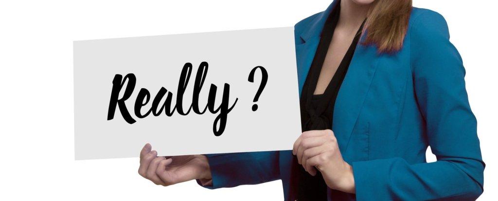 「本当?」というポスターを持つ女性