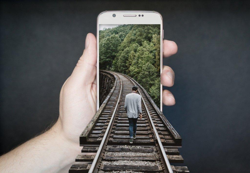 スマートフォンの中の道を進む男性