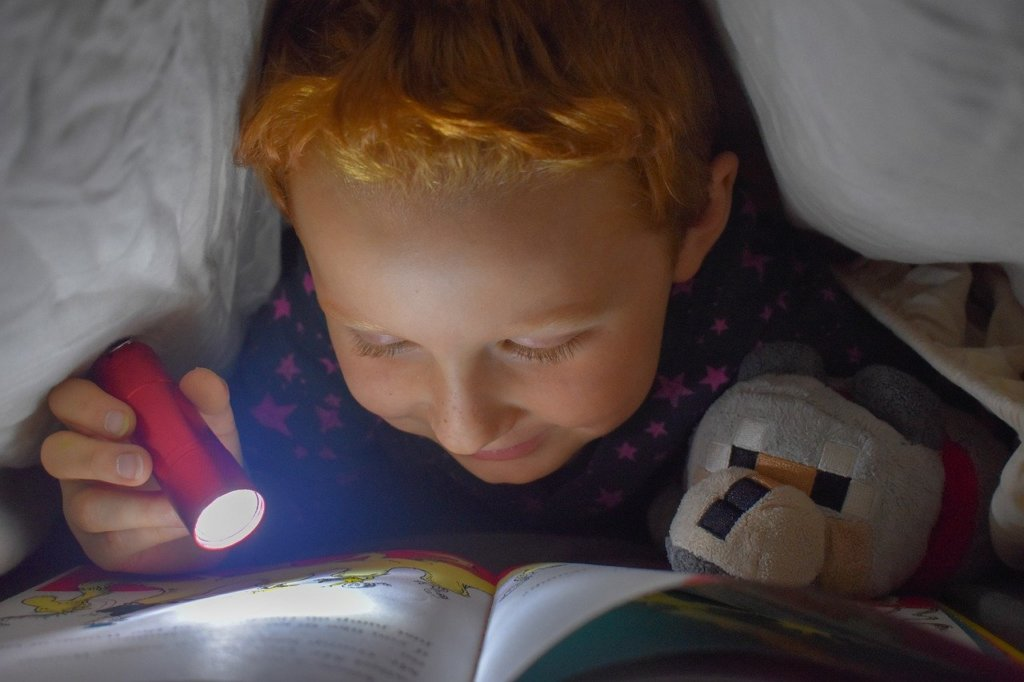 布団にもぐって本を読む少年