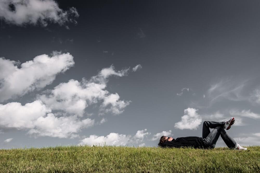 芝生に横たわって空を見上げる男性